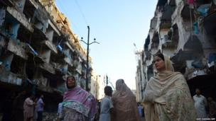 Pakistani people gather in front of their damaged homes at the site of a bomb blast in Karachi