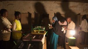 People cast their votes near the end of the day during the Kenyan general elections at the Wabera primary school in Isiolo, northern Kenya, 4 March 2013
