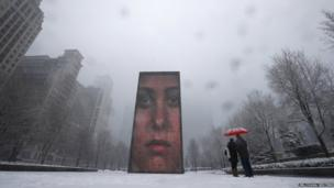 A couple take a pictures of an LED display on 50-ft tall glass towers, projecting images of faces in Chicago