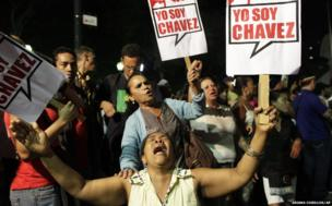 "A supporter of Hugo Chavez cries as she holds a sign that reads in Spanish ""I am Chavez"""