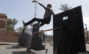 A protester opposing Egyptian President Mohamed Mursi throws stones at riot police