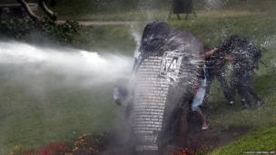 Students in Santiago protect themselves from a water cannon