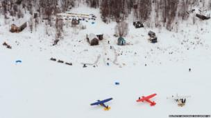 The lead group of Iditarod Trail Sled Dog Race mushers rest their dog teams in a wooded area at the historic checkpoint of Iditarod, Alaska
