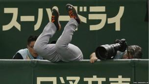 Netherlands' first baseman Curt Smith dives into photographers area