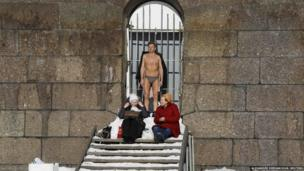 Man sunbathes while two women wrap up against the cold.
