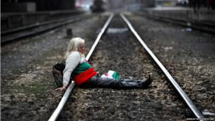 A protester sits on the tracks during a blockade of the railway next to Sofia Central railway