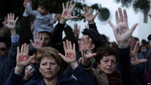 "Cypriots show their palms reading ""No"" during a protest against an EU bailout deal outside the parliament in Nicosia on Monday"