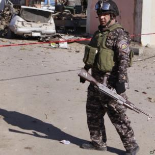 A policeman stands guard at the scene of a car bomb attack in the Shia stronghold of Sadr City