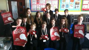 Caister High School stand before the camera with School Report posters in hand