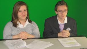 Two students sit behind the news desk