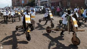 People take part in a tshukudu (wooden scooters) race in Goma in eastern Democratic Republic of Congo on 16 March 2013