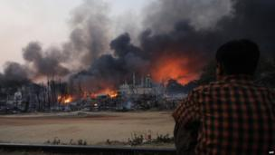 A resident watches as black smoke rises from burning houses in riot-hit Meiktila, central Burma on 21 March 2013