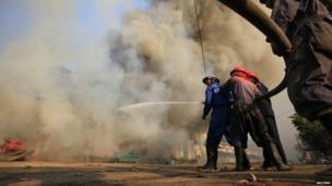 Firemen attempt to extinguish a fire during riots in Meiktila 22 March 2013