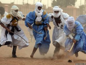 Men challenge for the ball during a game of hockey in M'Hamid El Ghizlane, Morocco
