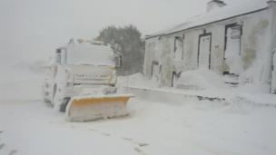 A snow plough and buildings in a snow drift. Photo: Matthew Wood