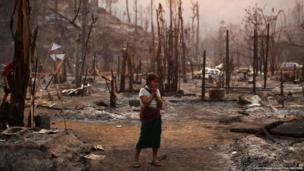 A survivor reacts as she stands in ruins of the burnt Ban Mae Surin refugee camp