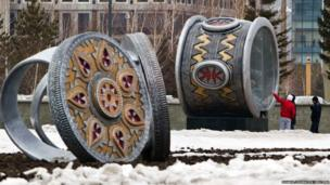 People look at art installations shaped in the form of Kazakhs national jewellery in Astana