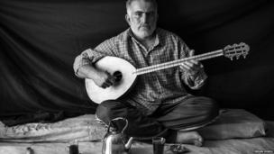 Omar, 37, plays his buzuq, an instrument which is also known as a long-necked lute