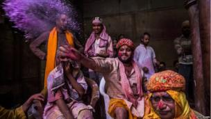A Hindu priest throws coloured powder at devotees during Holi celebrations,