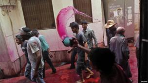 A boy flings coloured water on a group of men as they leave the Bankey Bihari temple after celebrating Holi in Vrindavan.,