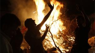A group of boys dance near a bonfire as they celebrate Holi, the Hindu festival of colours, in Allahabad, India ,