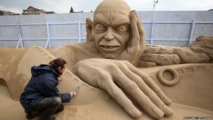 Radavan Zivny works on a sand sculpture of Gollum