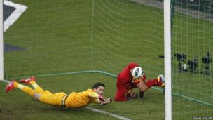 Spain's forward Pedro (right) falls down after scoring the winning goal past France's goalkeeper Hugo Lloris