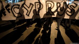 Protesters hold a banner that reads Hands off Cyprus during an anti-bailout rally outside European Union house in capital Nicosia, Cyprus