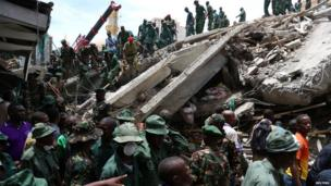 Rescuers search for survivors amongst the rubble of a collapsed building in the Kariakoo district of central Dar es Salaam, 29 March 2013