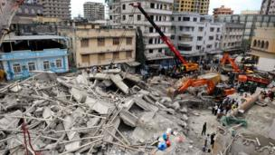 Rescuers using mechanical diggers remove rubble from the site of a collapsed building in Dar es Salaam, Tanzania, 29 March 2013