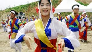 North Korean dancers perform to celebrate a South and North Korea joint ground- breaking ceremony to build an industrial park at Kaesong, 30 June 2003