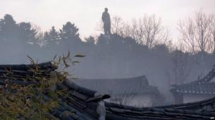 A large statue of Kim Il-Sung dominates the skyline at sunset over Kaesong, April 2011