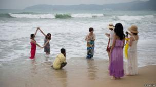 Tourists pose for photos in the Yalong Bay area of Sanya