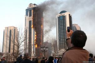 A man takes a picture of a burning skyscraper in central Grozny