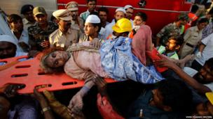 Rescue workers use a stretcher to carry a woman who was rescued a day after the collapse of a residential building in Thane district, on the outskirts of Mumbai