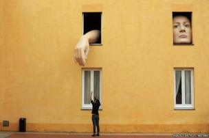 A woman takes pictures of art installation entitled, Alice, by Spanish artist Cristina Lucas