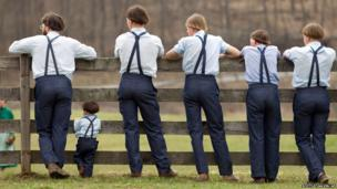 Amish boys watch a game of baseball outside the school house in Bergholz, Ohio