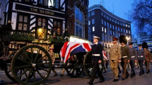 British military personnel escort a union jack-draped coffin on a gun carriage drawn by the King's Troop Royal Artillery during a rehearsal for the upcoming funeral of former British PM Margaret Thatcher