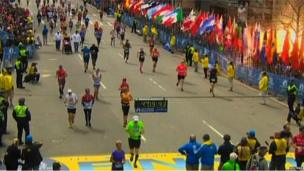 Competitors run as the first explosion is seen near the finish line of the marathon, Boston, 15 April 2013