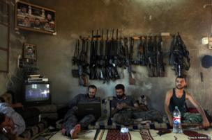 Free Syrian Army fighters sit in a house on the outskirts of Aleppo, Syria, 12 June 2012