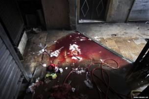 Blood and used medical supplies spill out of the back door of Dar al-Shifa hospital in Aleppo, Syria, 11 October 2012