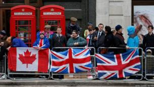 Spectators gather on the route to watch the funeral procession of former British prime minister Margaret Thatcher
