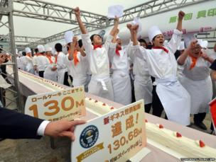 Confectionery college school students celebrate as they make the world's longest roll cake in Tokyo