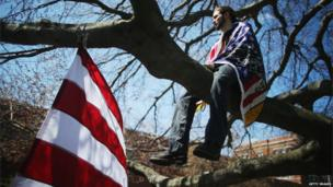 A mourner draped in the US flag watches on from a tree branch before the funeral for Krystle Campbell in Medford, 22 April