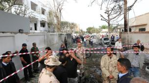 Libyan security forces gather outside the French embassy (L) in Tripoli following a car bomb blast, on April 23, 2013. A car bomb blasted the embassy of France in Tripoli, injuring two French guards and causing serious damage to the building, embassy and Libyan sources said. AFP PHOTO/MAHMUD TURKIAMAHMUD TURKIA/AFP/Getty Images