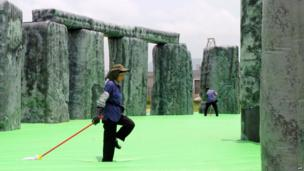 Workers clean Jeremy Deller's inflatable Stonehenge installation in Hong Kong (24 April 2013)