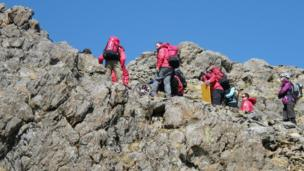 Mountain rescue team members guard the edge of a rocky slope as a rider makes slow progress