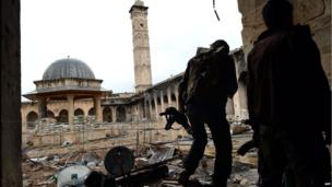 Syrian rebel fighters in the courtyard of the Umayyad Mosque, with the minaret still standing (16 April 2013)