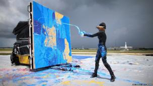 Artist Princess Tarinan von Anhalt throws paint into the flow of air coming from the engine of a Learjet engine