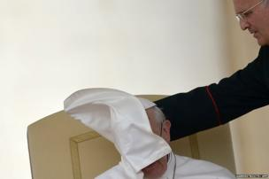 A cleric helps Pope Francis